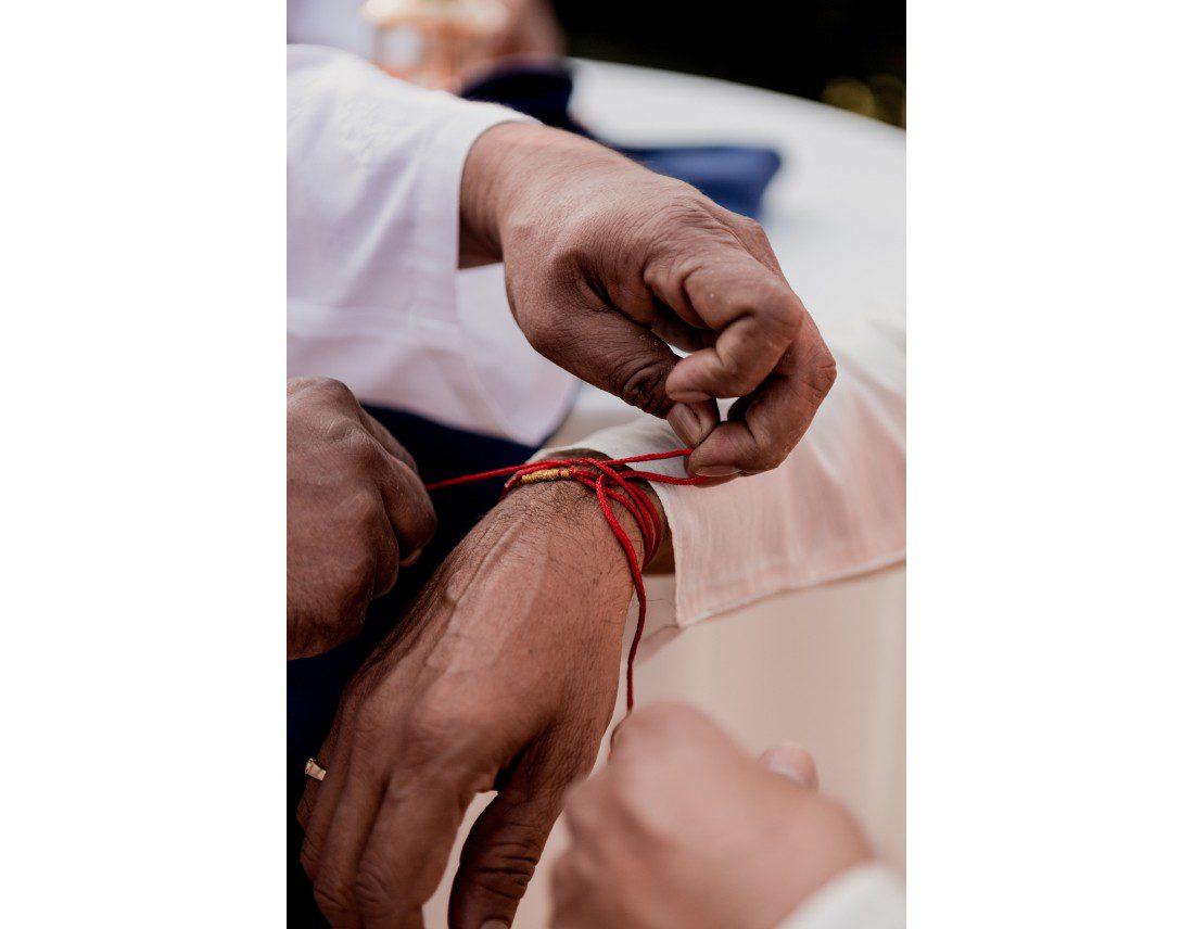 Bracelet rouge nommé Kalawa, au poignet des ivnités masculins.