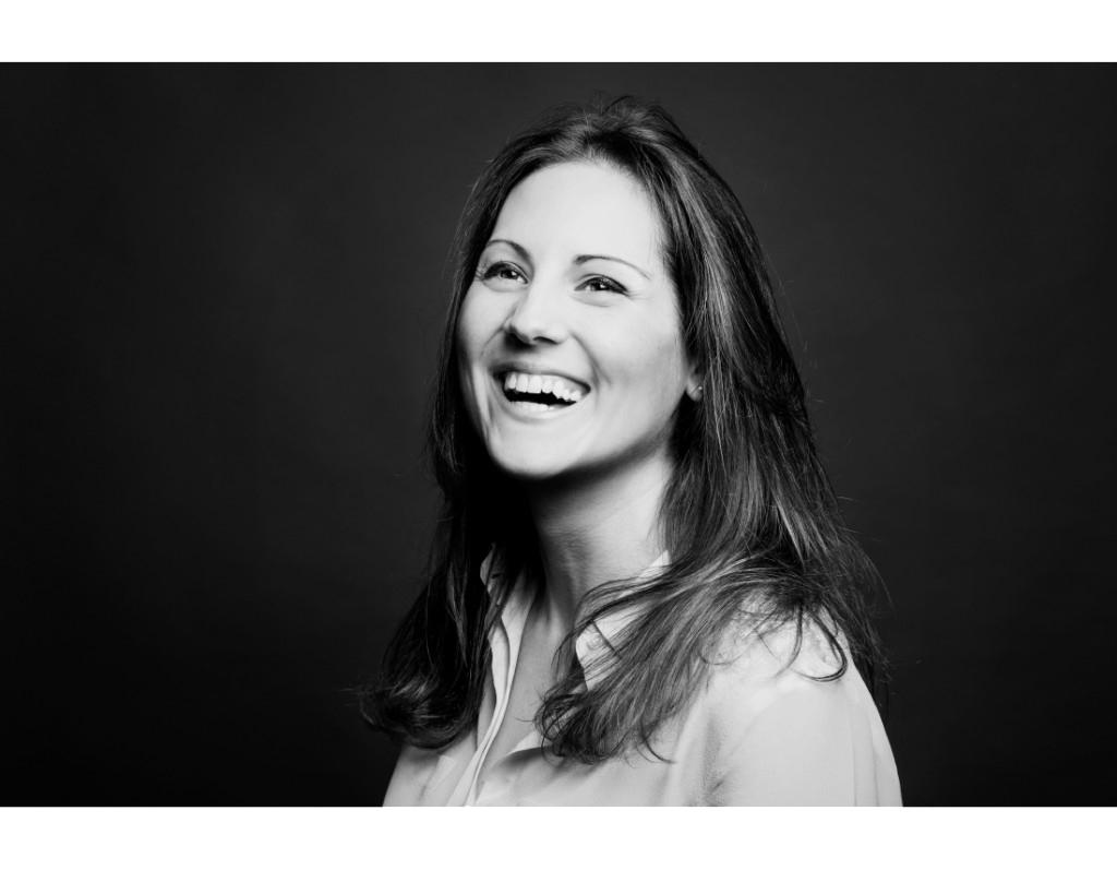 Portrait d'une femme souriant en noir et blanc en studio