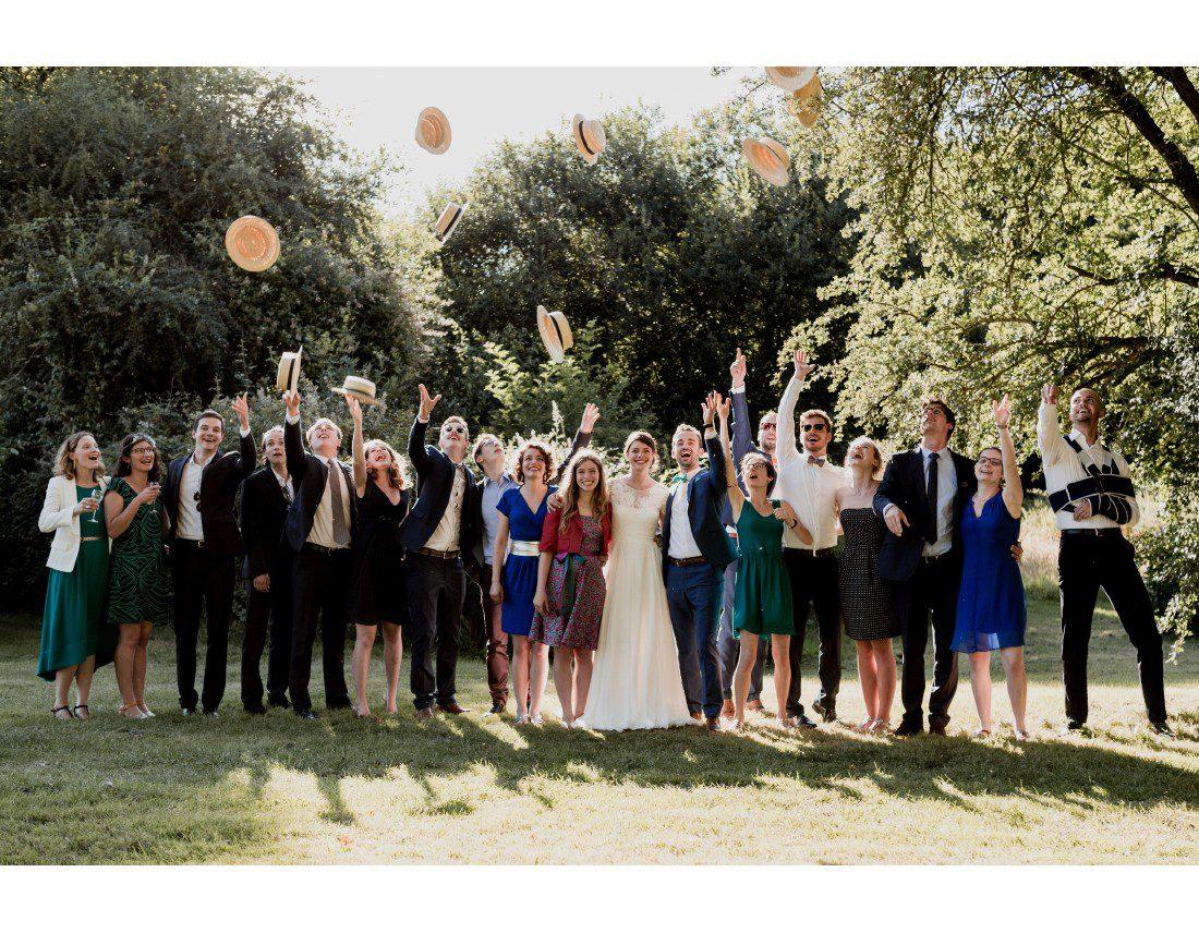 Photo de famille lors d'un mariage avec chapeau lancés en l'air.