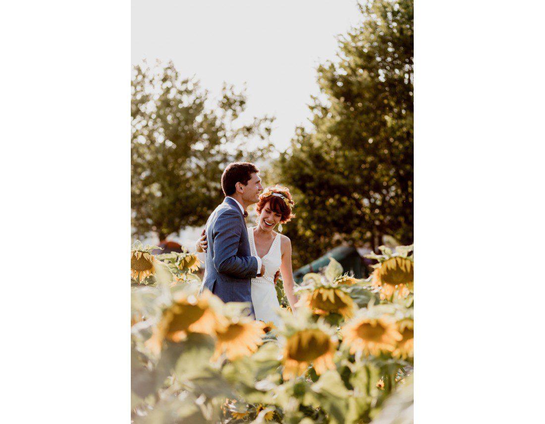 Couple de mariés dans un champ de tournesols.