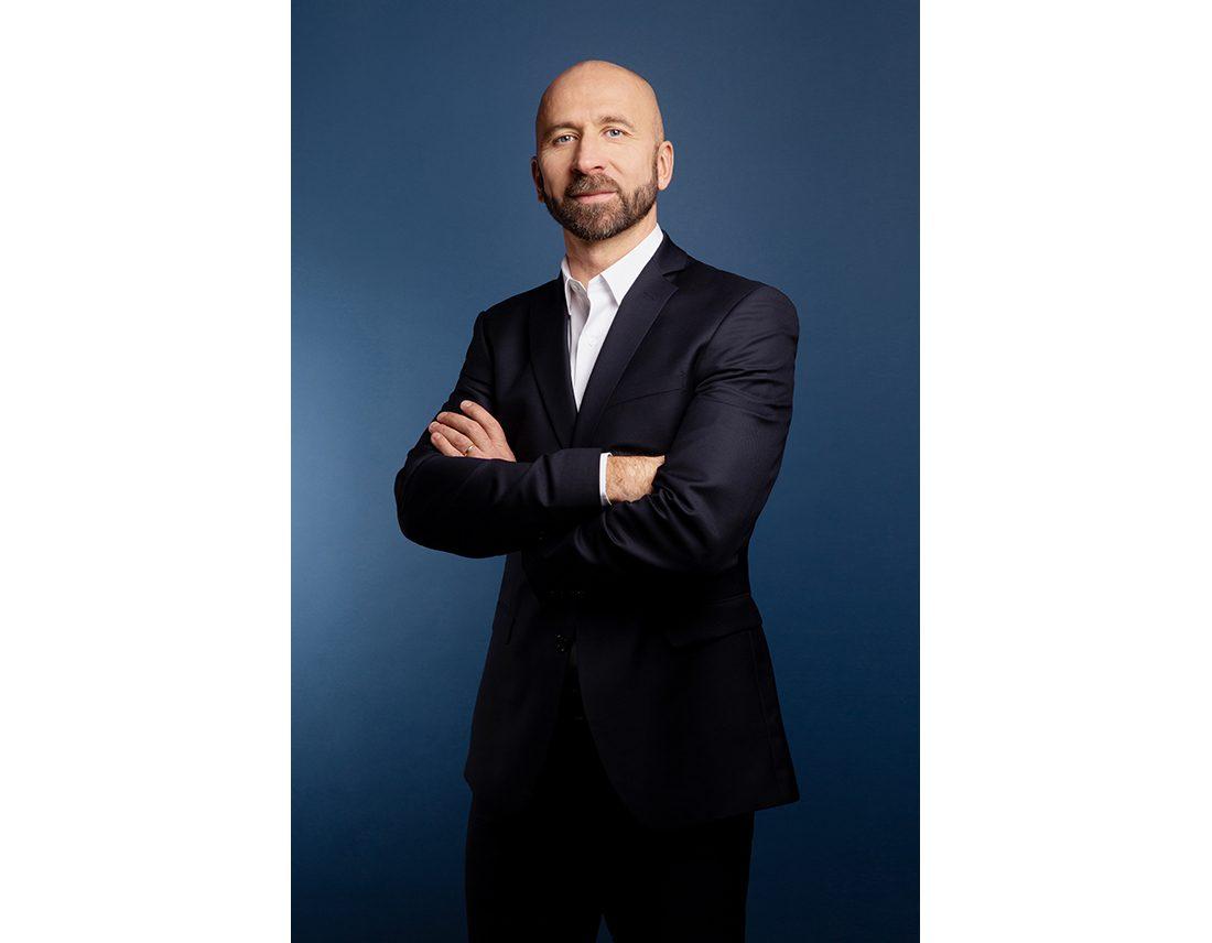 Portrait corporate d'un homme chauve avec barbe sur fond bleu en studio corporate