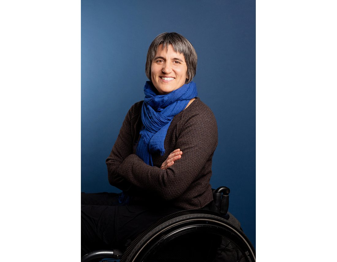Portrait de Emmanuelle Assmann en fauteuil roulant sur fond bleu, handicap, style corporate
