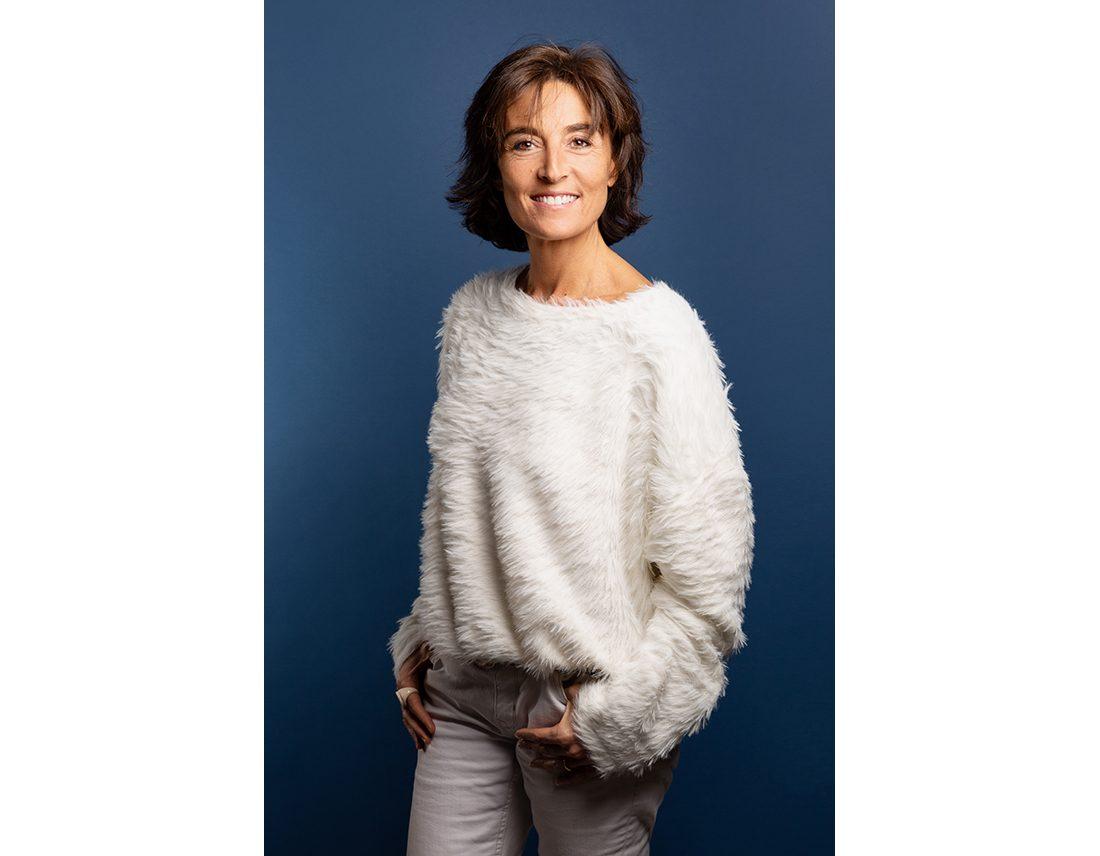 Portrait de Nathalie Lanetta sur fond bleu style corporate