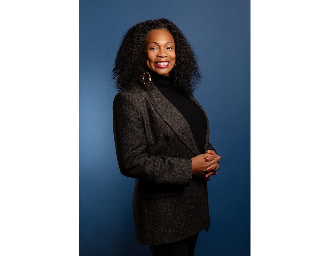 Portrait de la ministre Laura Flessel sur fond bleu style corporate