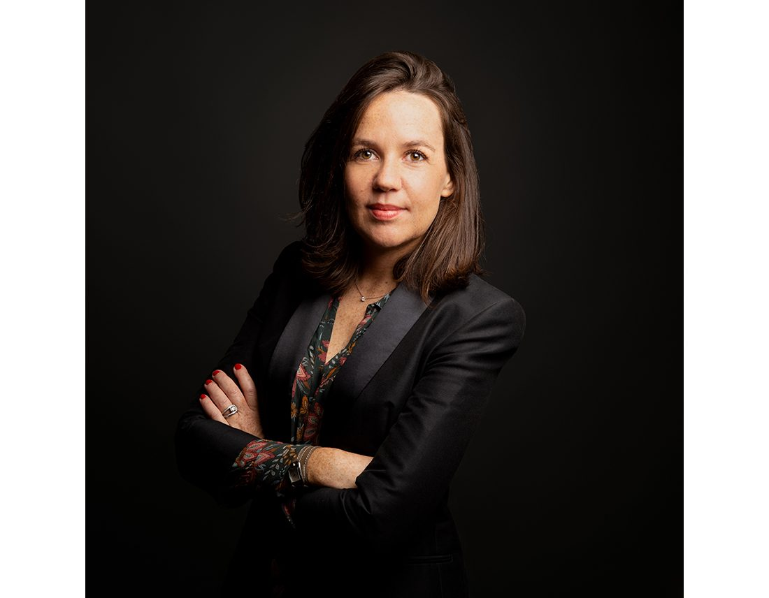 Portrait d'une avocate en studio, bras croisés, corporate en studio sur fond sombre