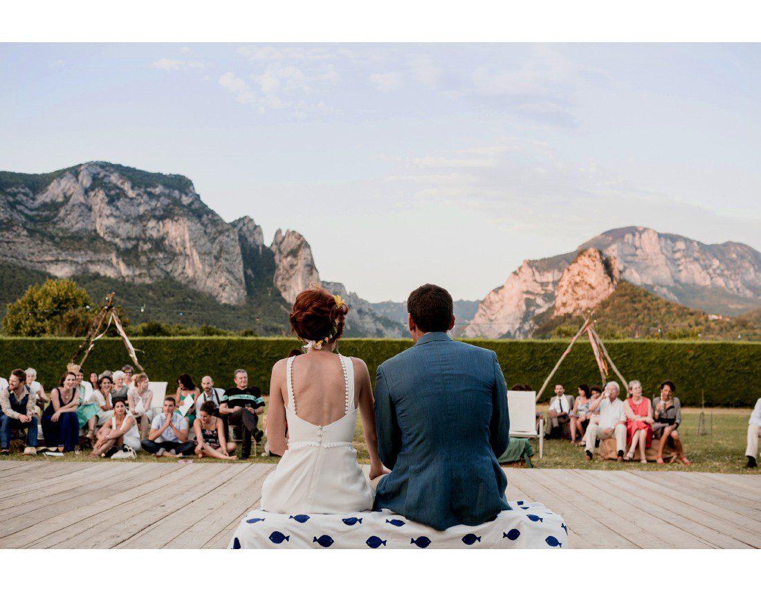 Mariés assis de dos face aux montagnes.