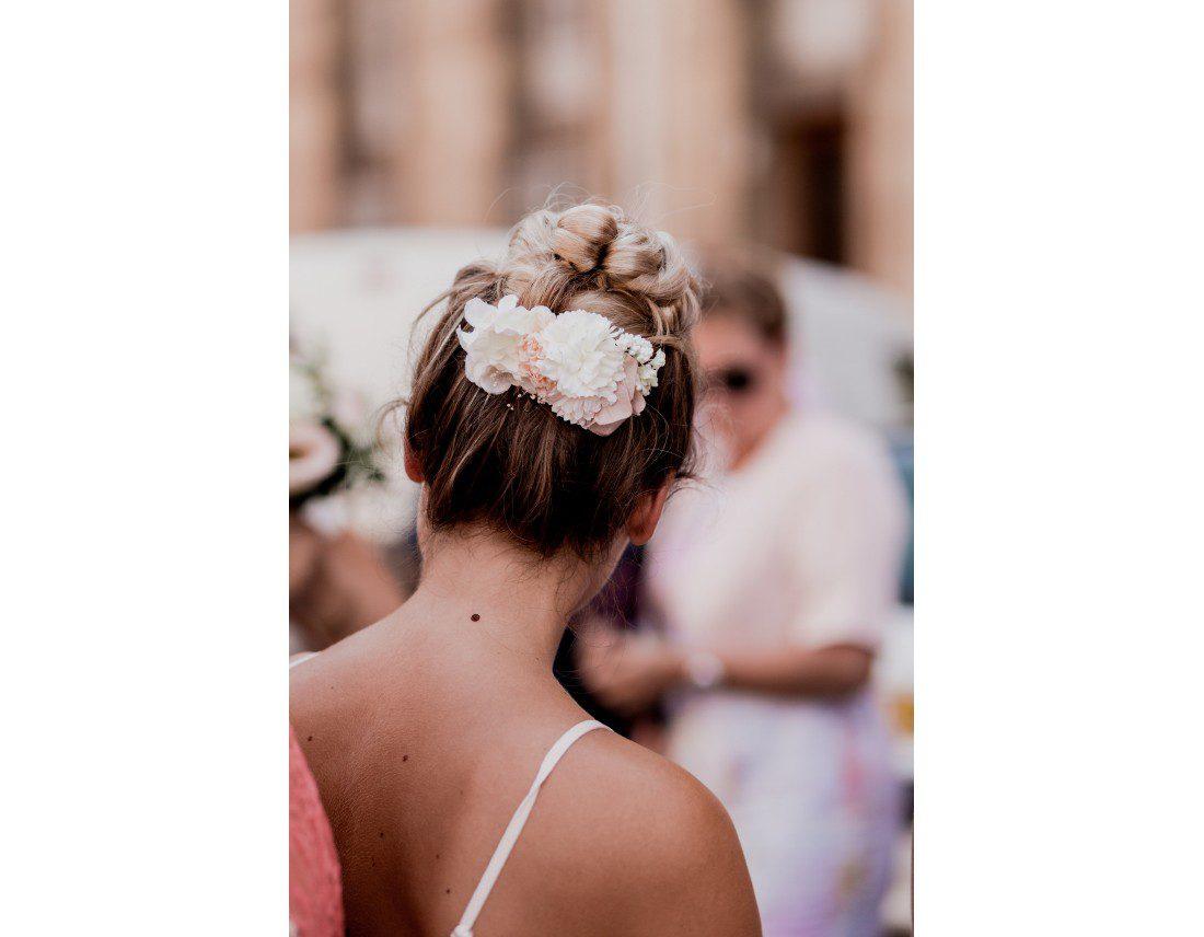 Fleurs dans les cheveux d'une invitée, jolie nuque.