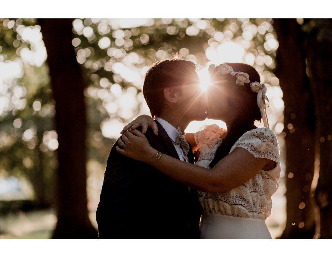 Bisou de mariés dans le soleil golden hour.