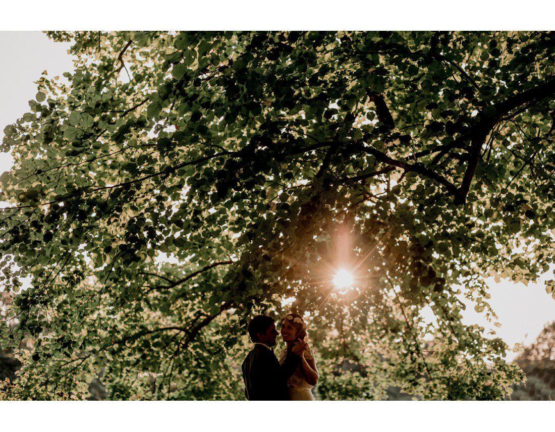 Couple de mariés dans le soleil couchant et arbres.