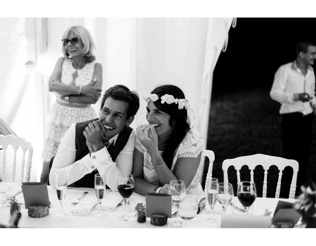 MAriés riant a un discours pendant leur mariage