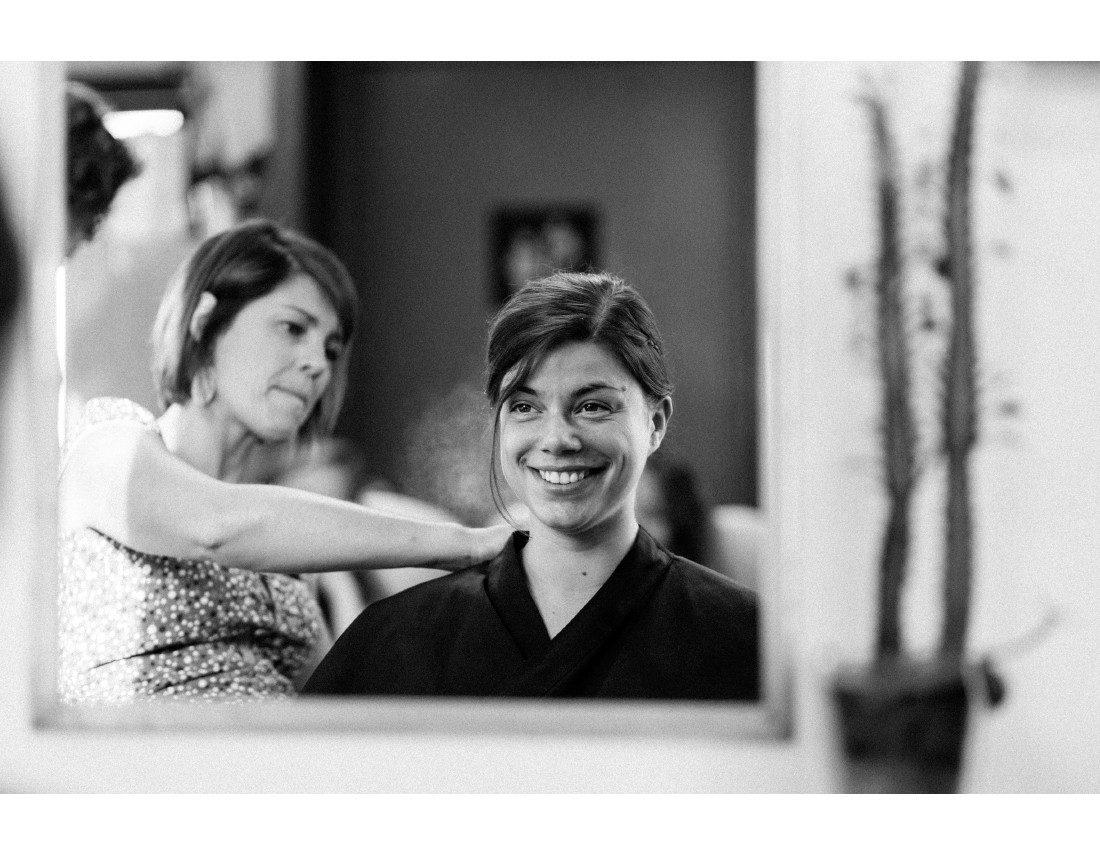 Future mariée qui sourit pendant la coiffure.