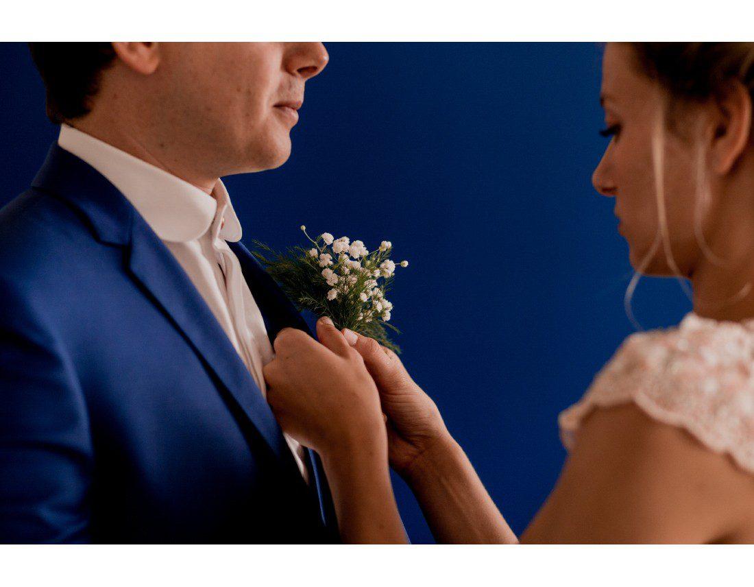 La mariée met la boutonniere de son futur mari.
