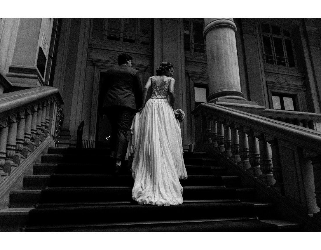 couple montant l'escalier d'honneur de la mairie du 10e arr de Paris.