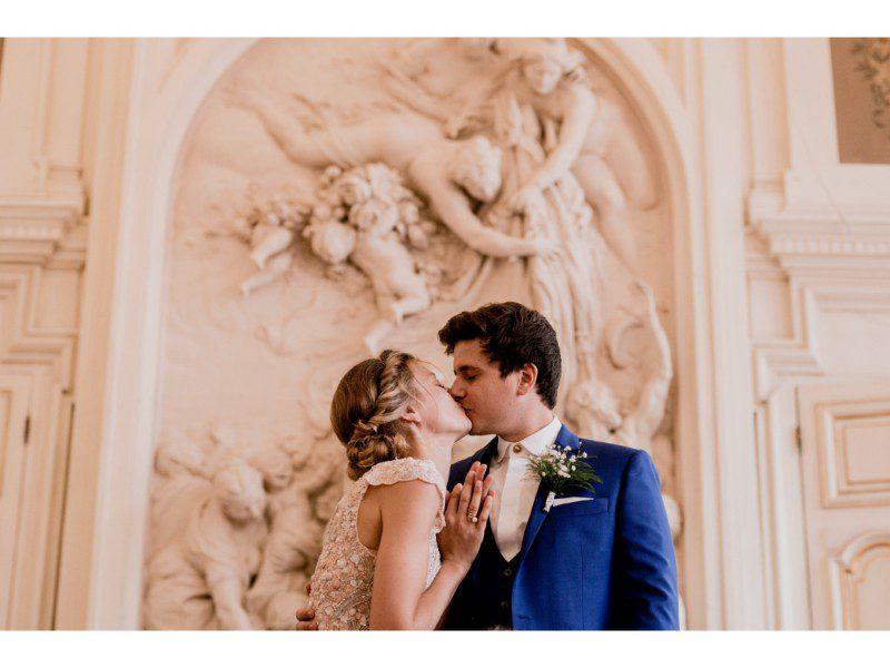 Couple qui s'embrassse pendant leur mariage a la mairie du 10e à Paris.