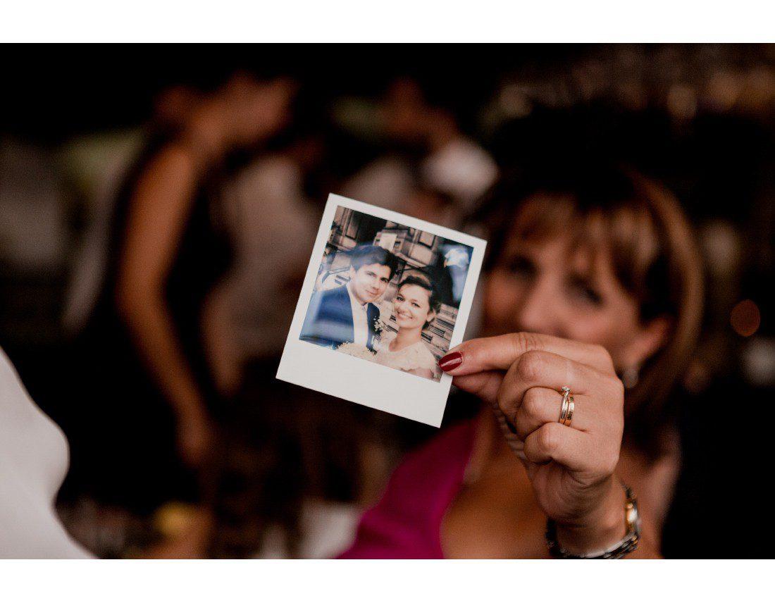 Invitée qui montre un polaroid de mariage.