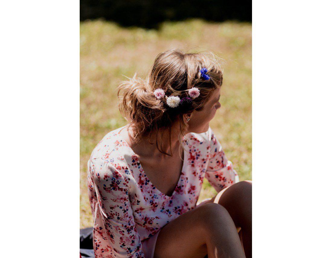 Invitée avec des fleurs dans les cheveux pour un mariage champêtre.