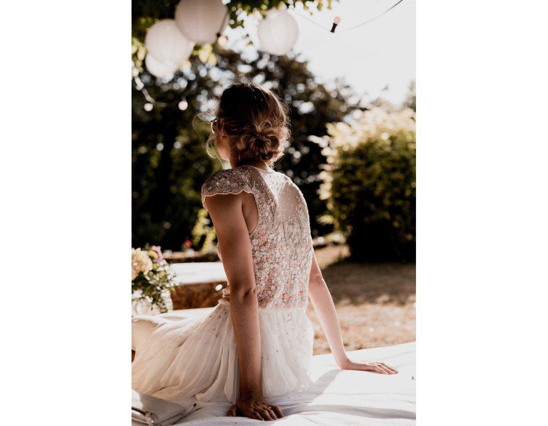 La mariée de dos avec sa robe brodée de perles.