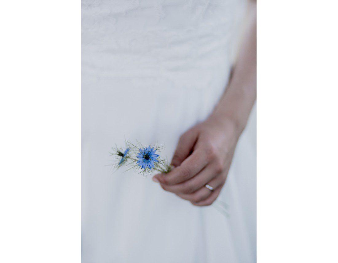 Fleur de nigelle dans la main d'une mariée.