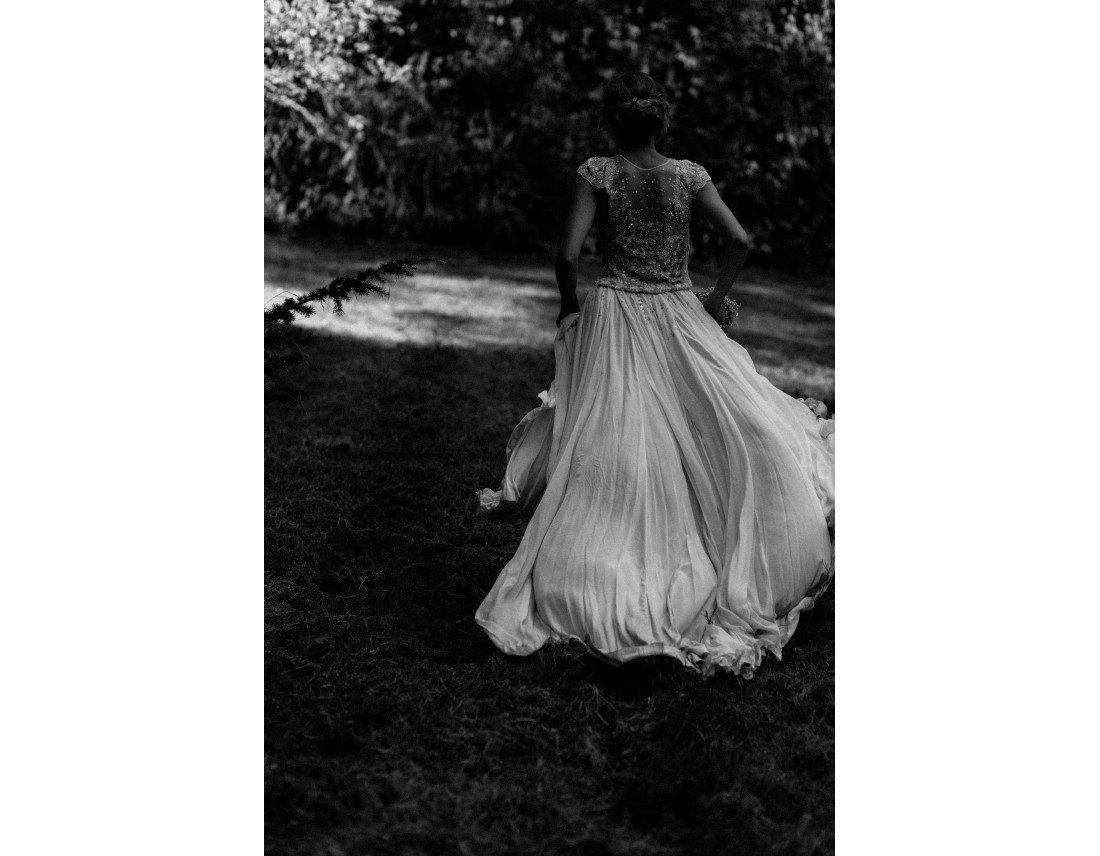 Mariée qui court dans un jardin, jupe qui vole.