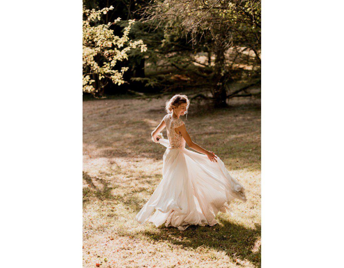 Mariée qui danse dans le soleilavec sa robe.