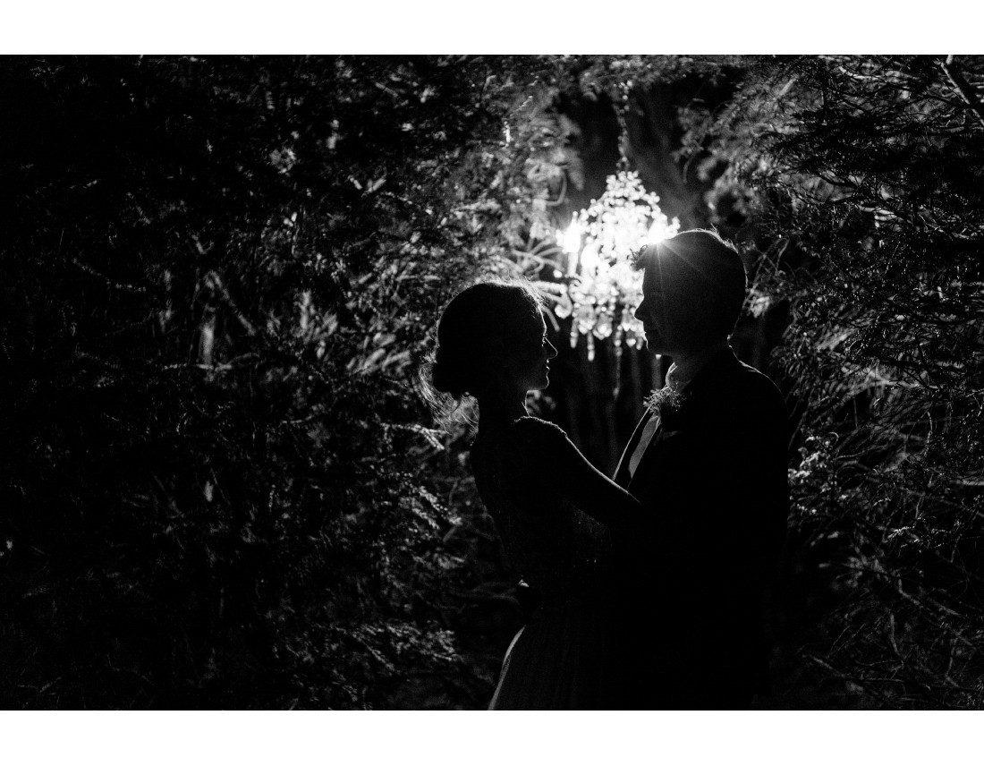 Couple de mariés dans la nuit avec un lustre cristal.