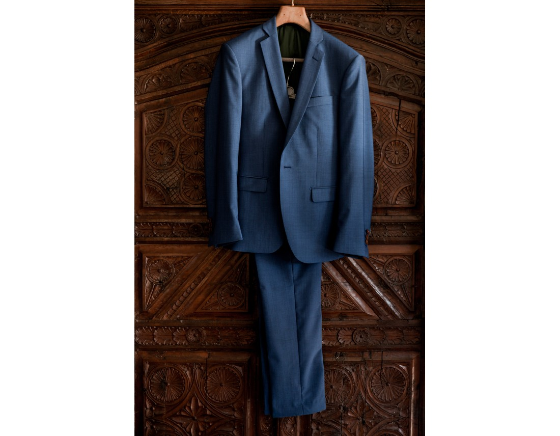 Costume bleu du marié suspendu a une armoire.