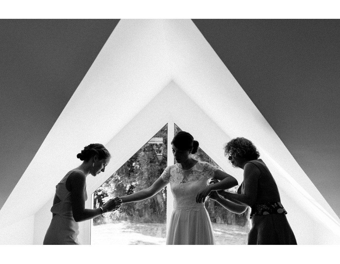 Habillage de la mariée devant une fenetre triangulaire.