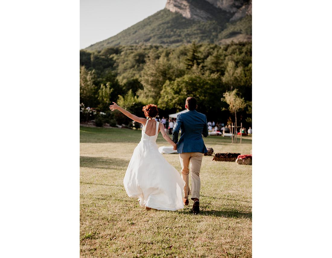 Couple de mariés qui courrent dans un jardin.