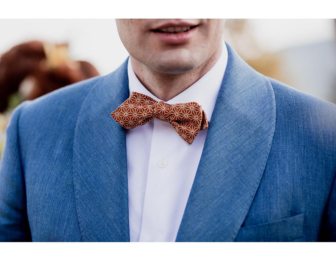 detail de tenue du marié. Costume bleu clair. Noeud papillon moutarde