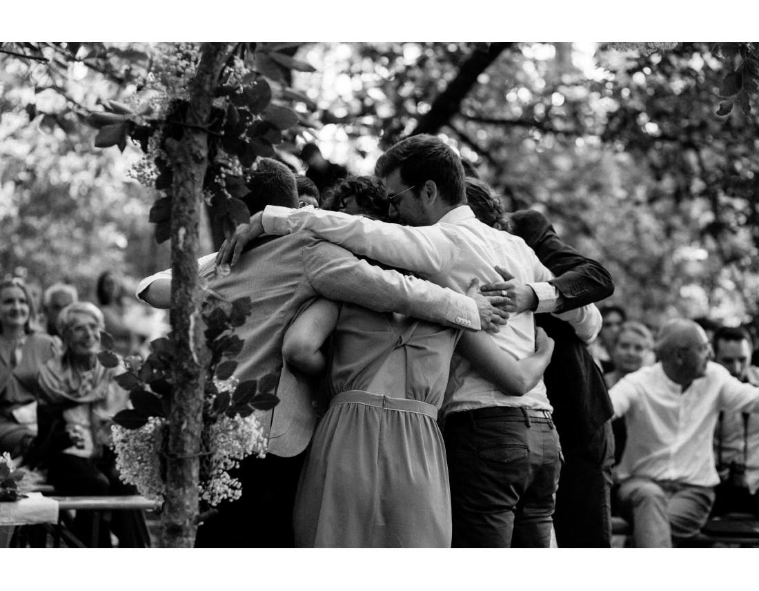 Groupe d'amis s'etreignant, calin general pendant mariage lesbien.