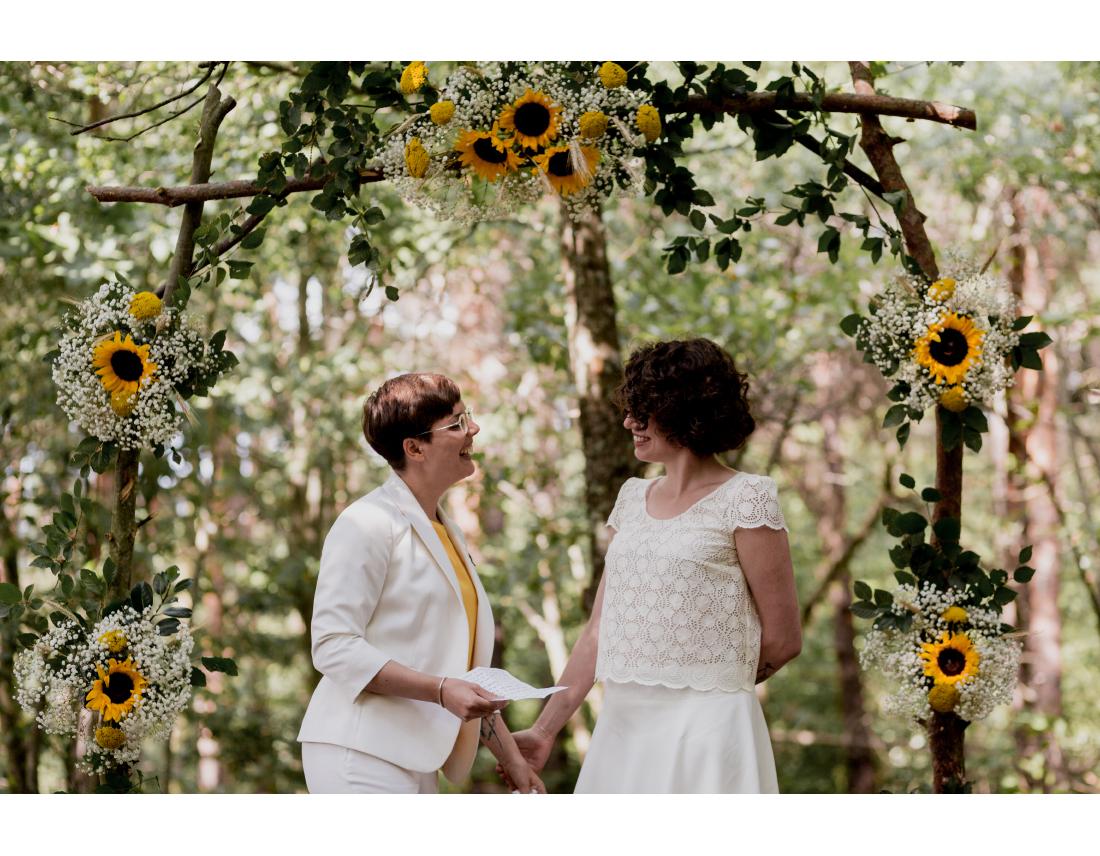 Echange de voeux sous l'arche fleurie de tournesol pendant ceremonie laique de mariage lesbien.