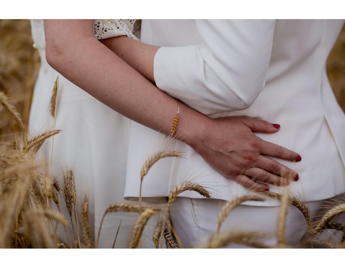 Mains de couple de femmes dans champ de blé, mariage lesbien