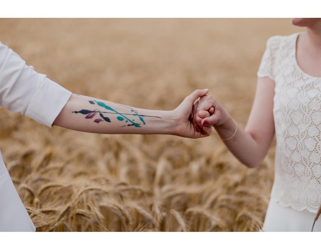 Tatouage sur le bras, Couple de femmes dans champ de blé, mariage lesbien