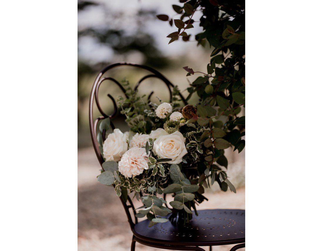 Bouquet de la mariée sur uen chaise en fer forgé