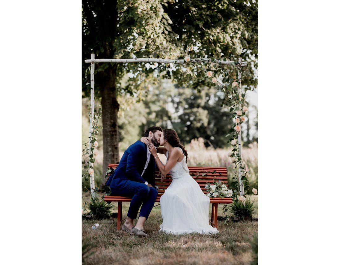 Couple s'embrasant pendant leur mariage, ceemonie laique en exterieur.
