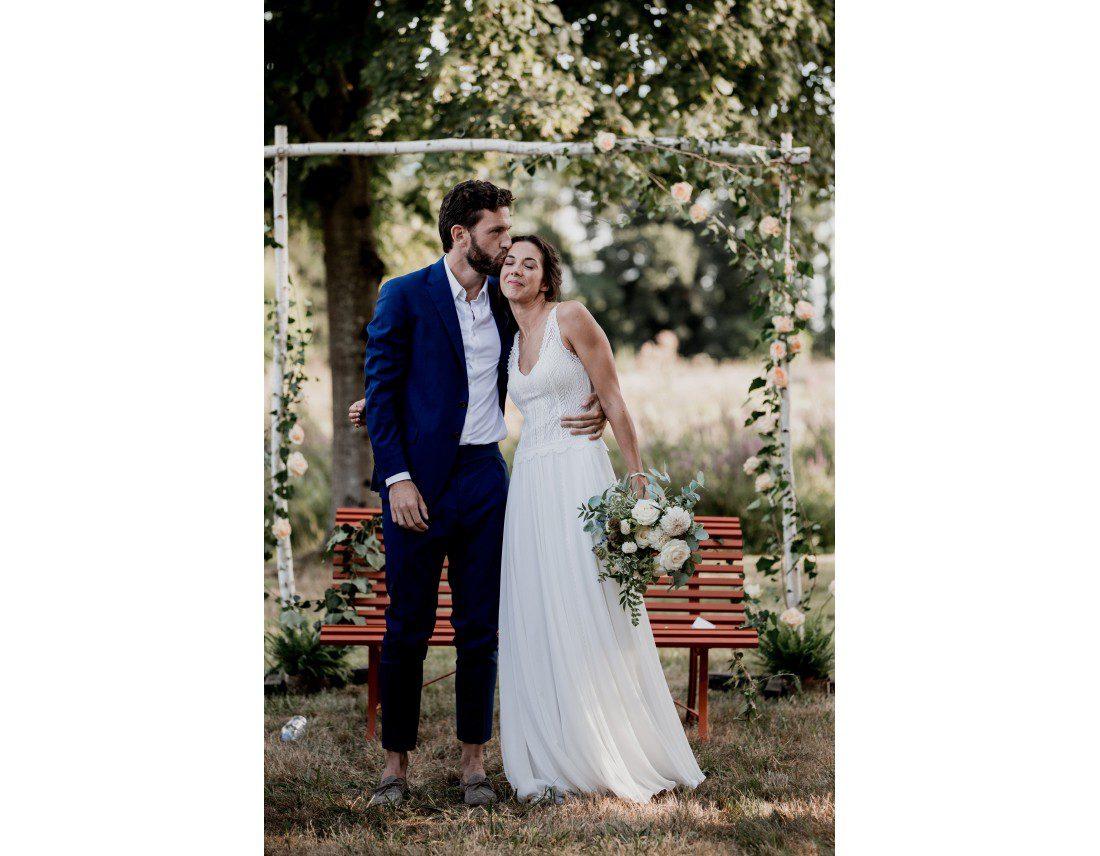 Marié embrassant sa femme sur la tempe pendant mariage.
