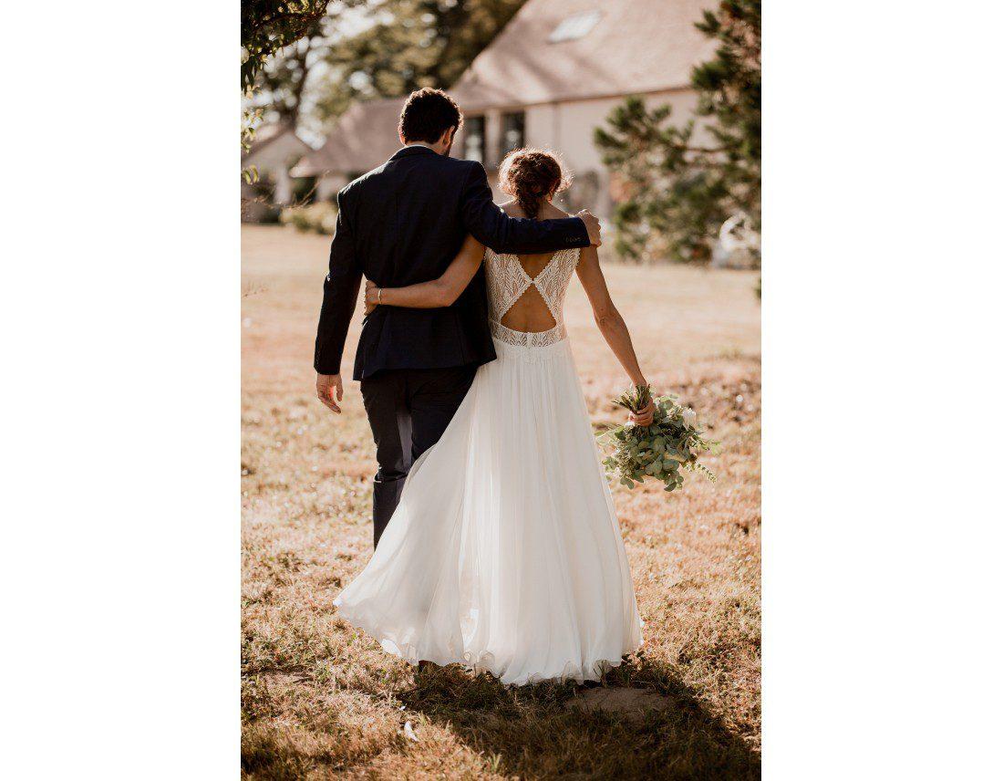 Mariés de dos dans la lumiere couchant et vent dans la robe