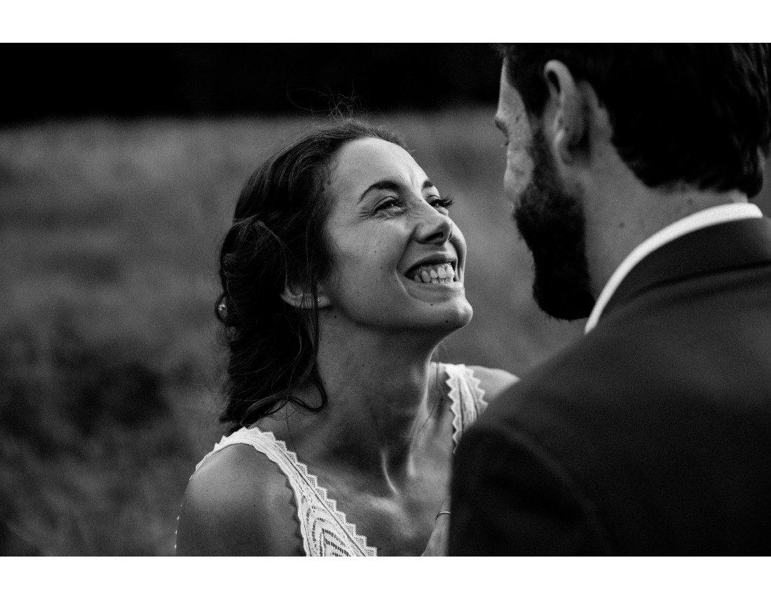 Mariée qui rigole en regardant son mari.