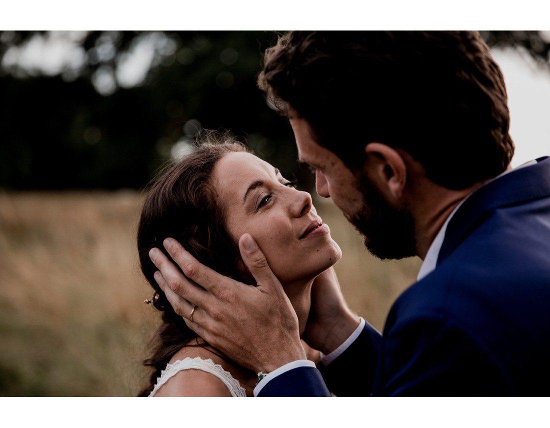 Marié qui embrasse sa femme en lui tenant le visage.