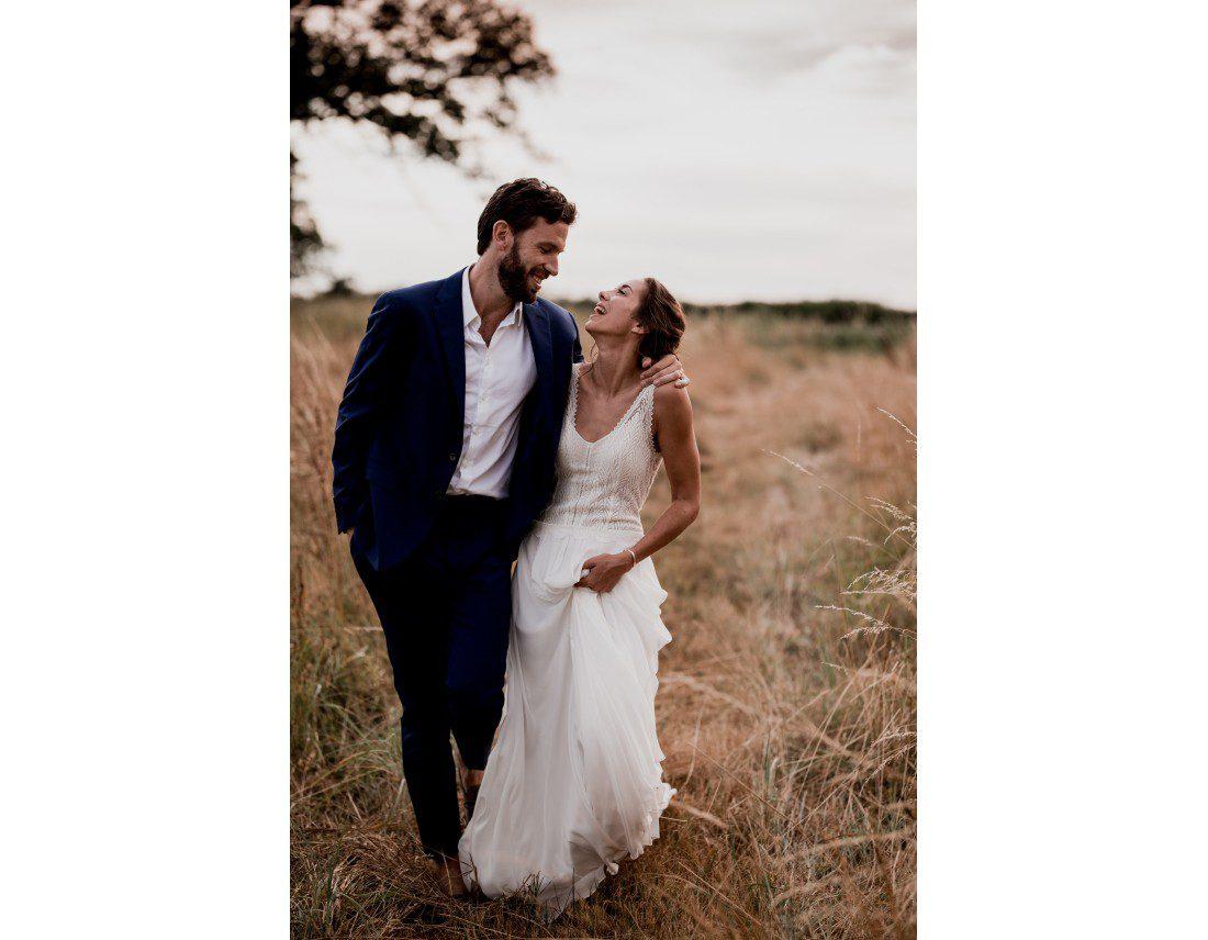 Couple marchant dans un champ en fin de journée.