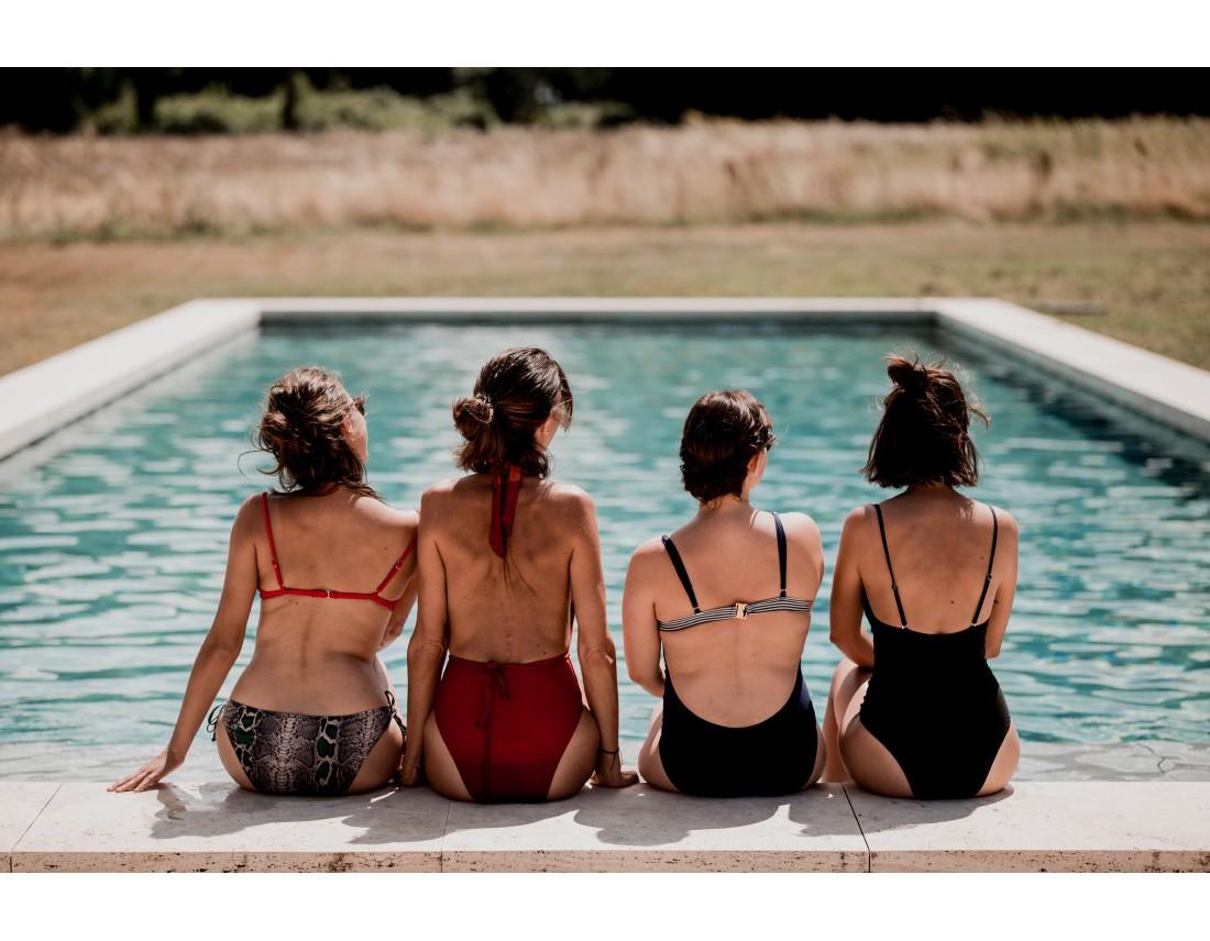 4 filles de dos en maillot au bord de la piscine