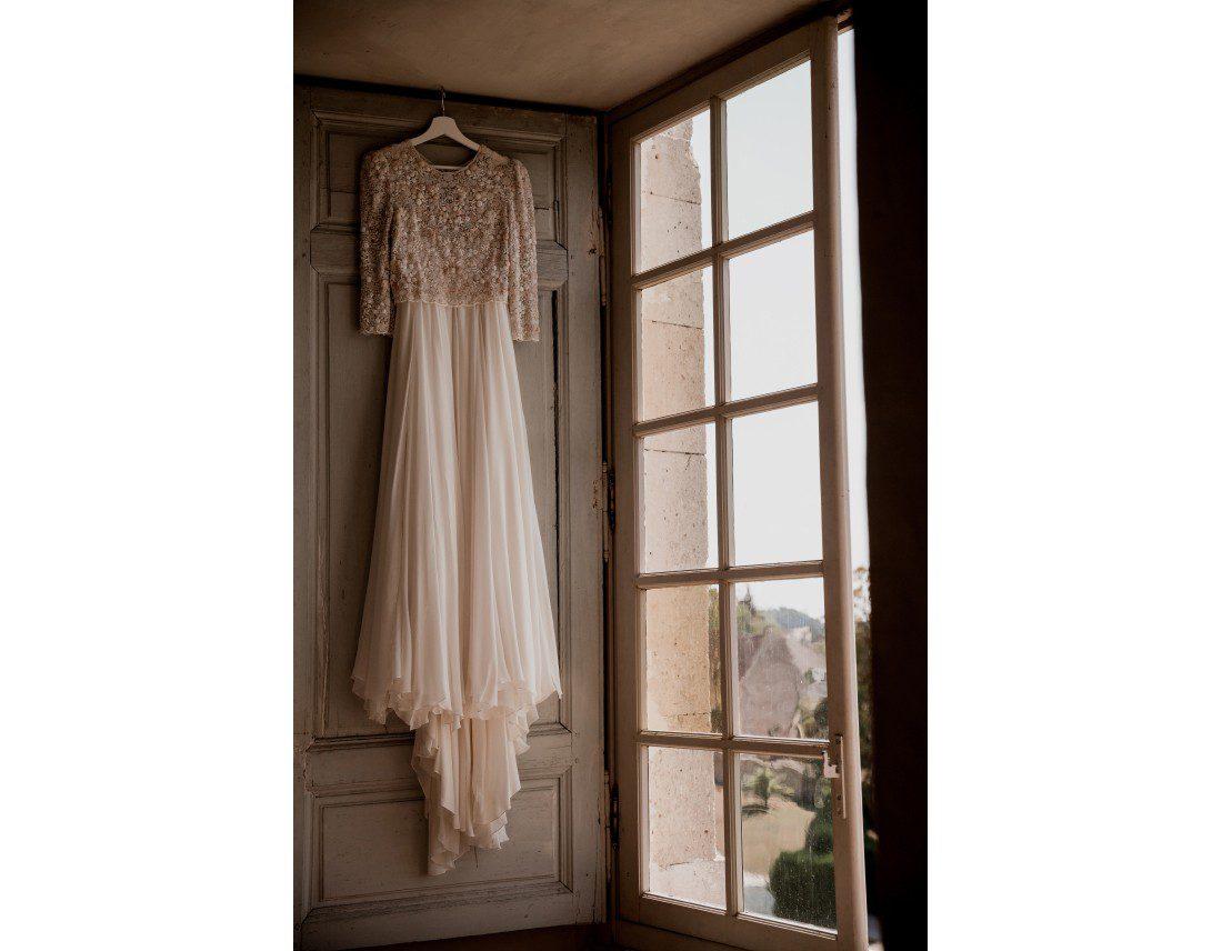Robe de la mariée suspendue a uen fenetre.