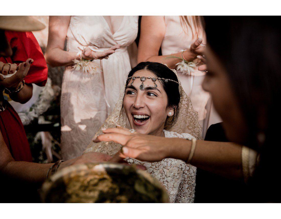 Mariée riant pendant la ceremonie du hénné.