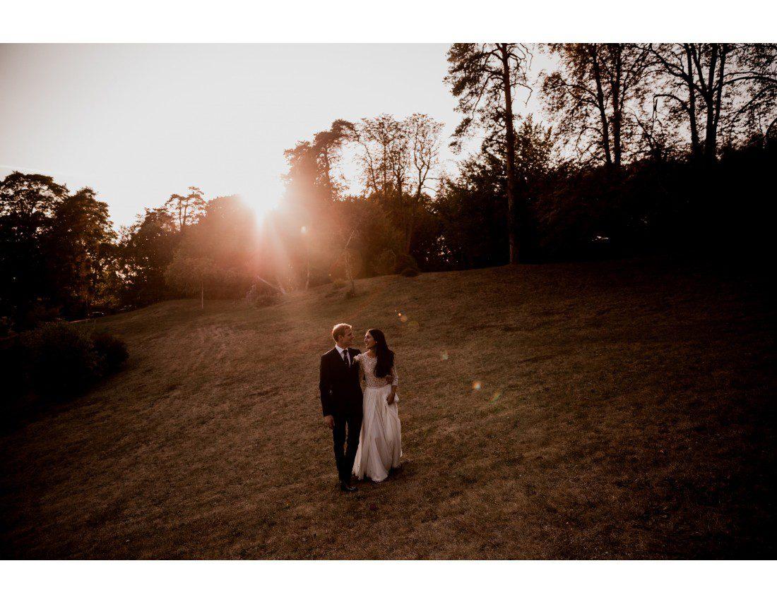 Mariés marchant dans le soleil couchant.