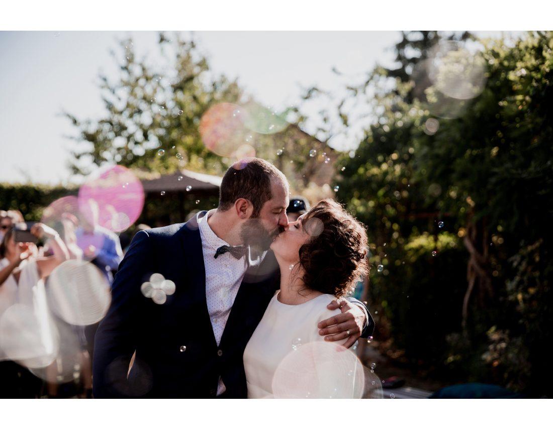 Couple de amriés s'embrassant a la fin de leur cérémonie de mariage, sous les bulles de savon.