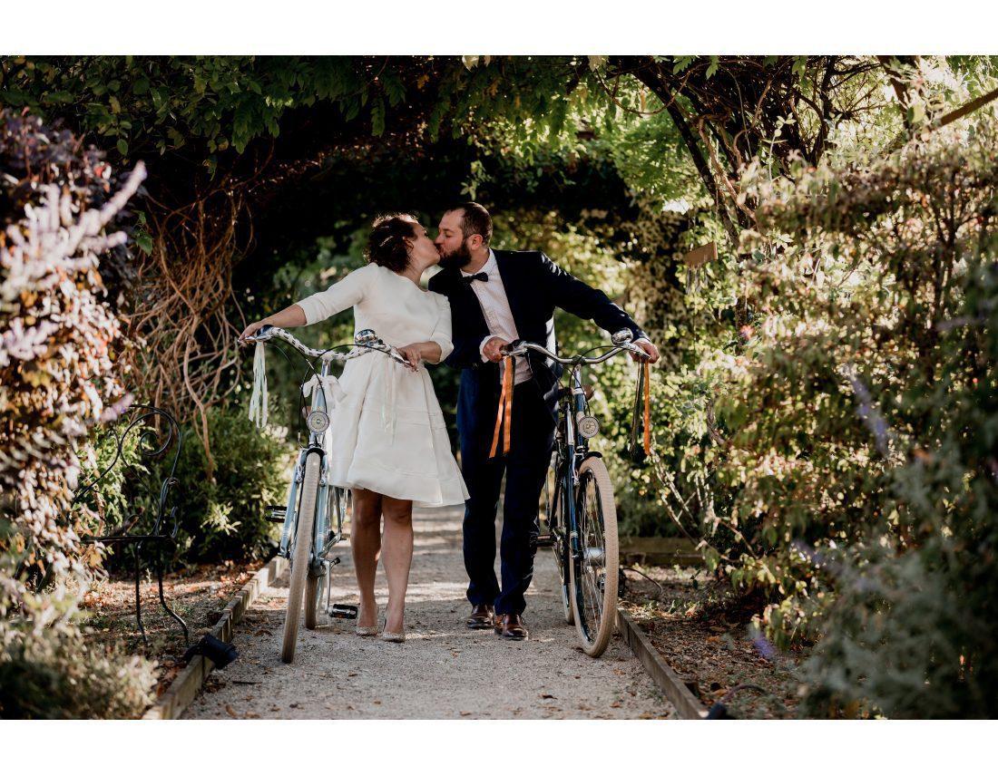 Couple s'embrassanta vec velos anciens lors de leur mariage.