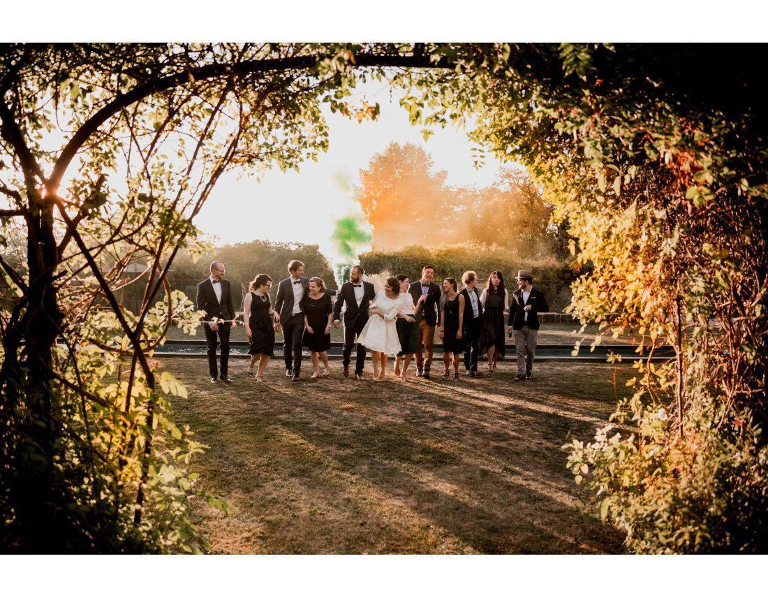Groupe d'amis avec fumigenes au coucher de soleil lors dun mariage