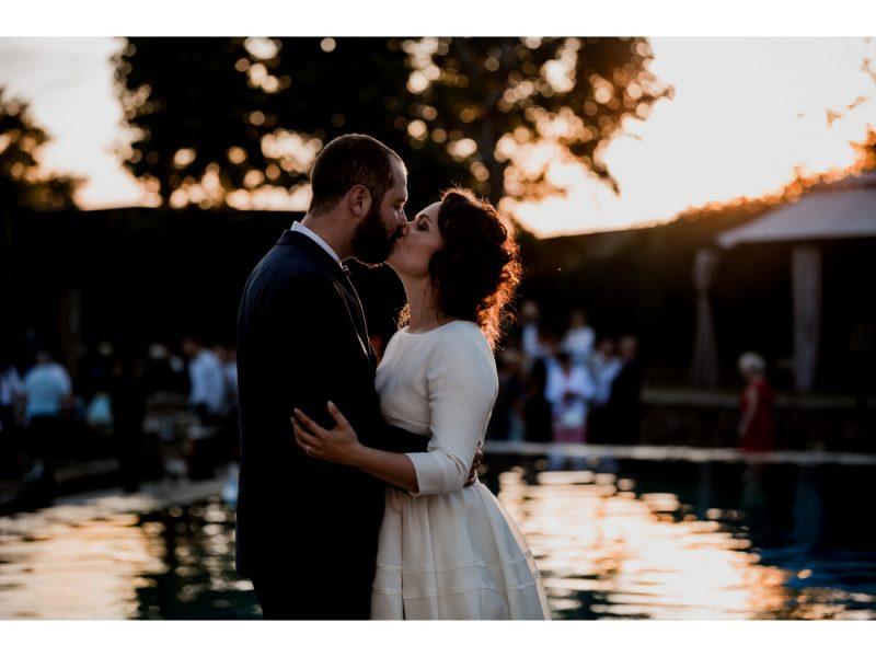 Couple de mariés qui s'embrasse au coucher de soleil devant la piscine du chateau de courban.