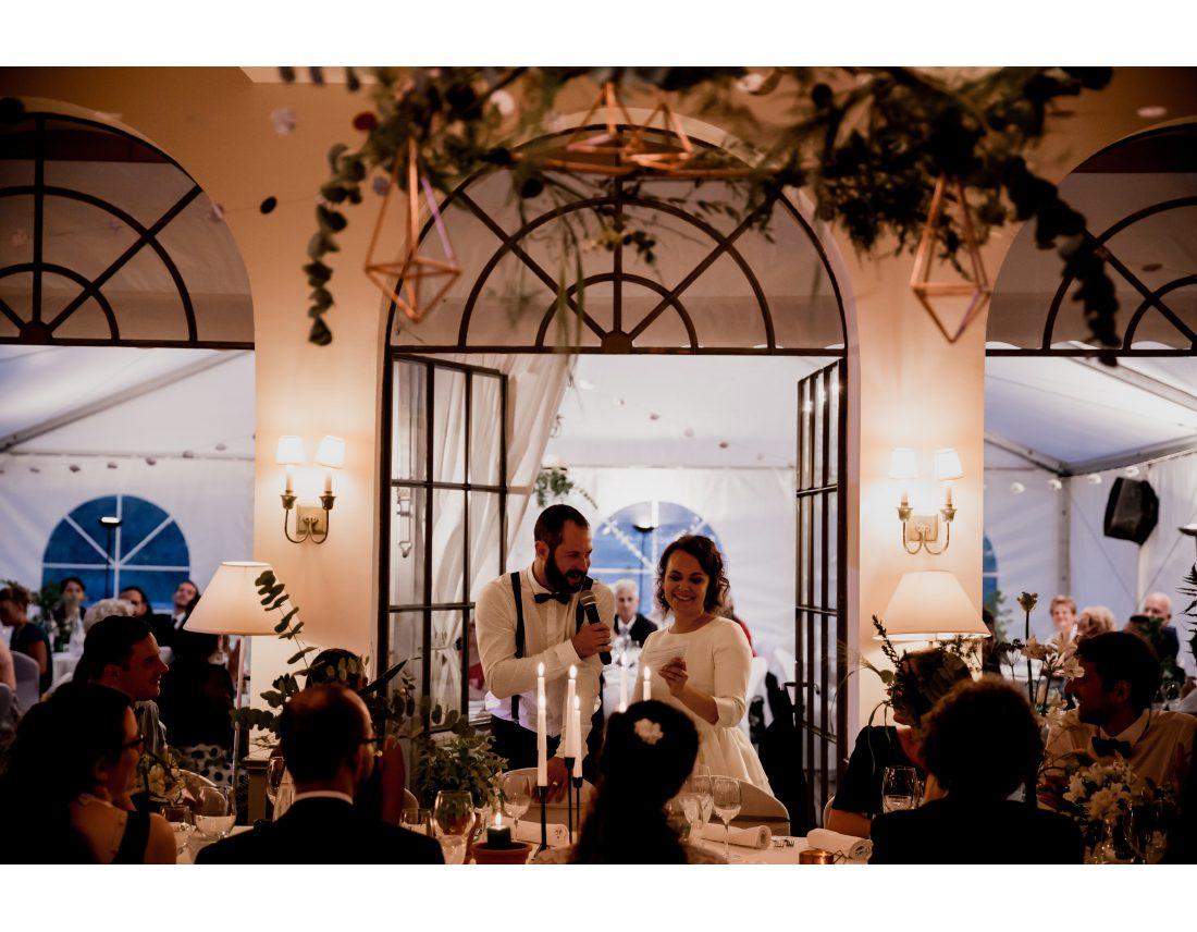 Couple de marié faisant un discours lors de leur diner de mariage.