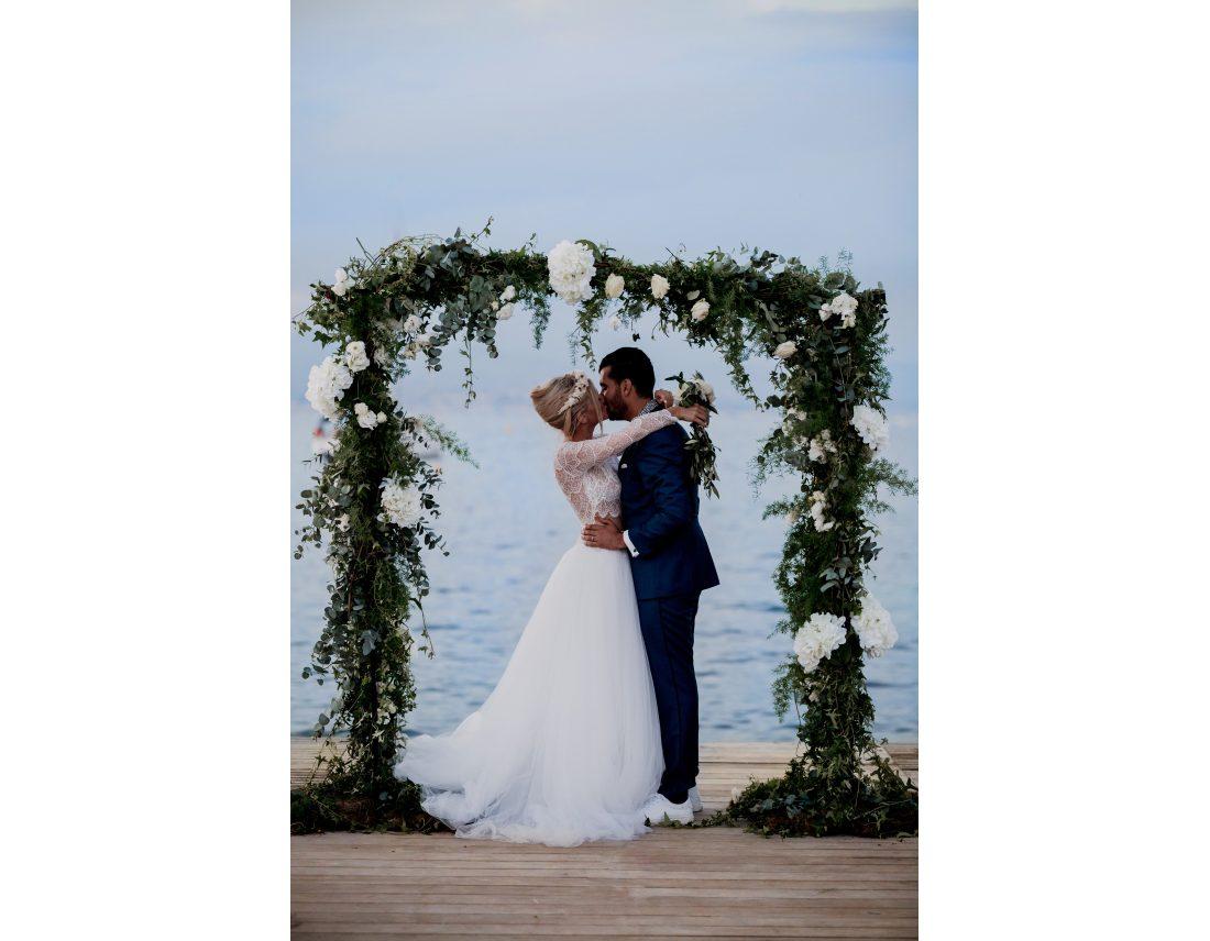 Couple s'embrassant sous une arche de fleur devant la mer.